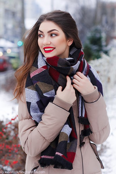 Young woman wearing a think patterned scarf a coat and gloves in the snow
