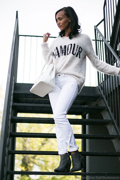 Woman walking down outdoor stairs wearing cuffed white jeans, gray booties, a tucked cream sweater, and a cream leather purse.