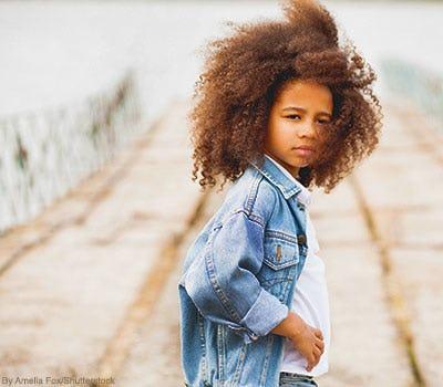 Little girl wearing light faded denim jacket.