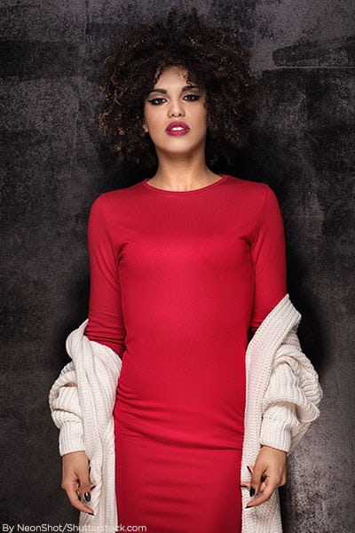 Woman in red bodycon dress and white sweater.