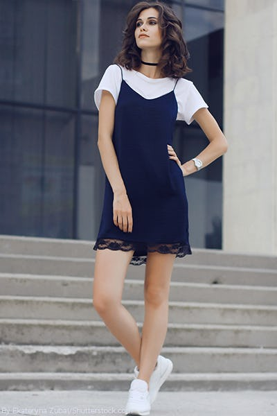 09a83909e32 Young woman wearing a navy slip dress with a white t shirt underneath