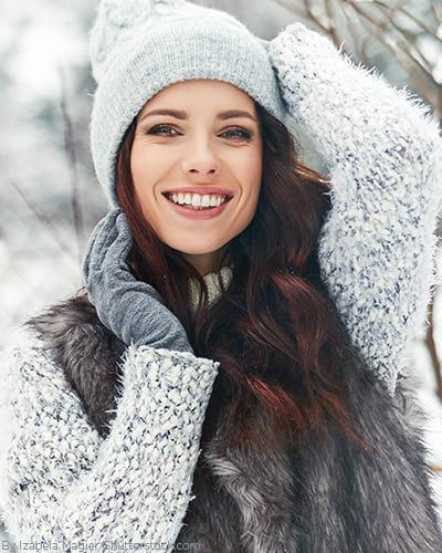 Young woman in the snow wearing a beanie, gloves and scraf