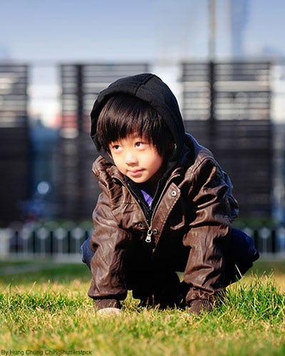 Little boy in brown leather jacket outside.
