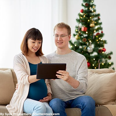 Man and his pregnant wife using a tablet on Christmas.