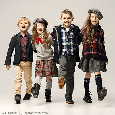 A group of young kids wearing preppy clothes and girls wearing skirts and thick boots socks with their boots