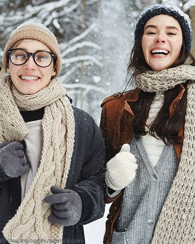 Two woman in the snow wearing layers of cardigans