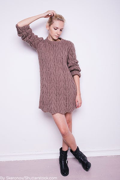 Woman wearing taupe chunky knit sweater dress with moto boots.