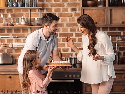 Dad and daughter giving mom a homemade cake