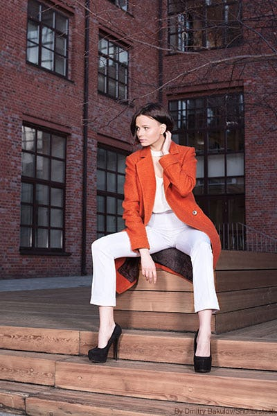 Fashionable woman wearing cropped flared white denim with black pumps and a poppy orange trench coat.
