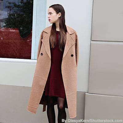 Fashionable woman wearing a long camel coat over a burgundy dress and sheer black tights.