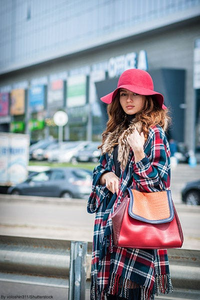 Woman in the city wearing a plaid ruana, scarlet floppy hat, and a red leather bag.