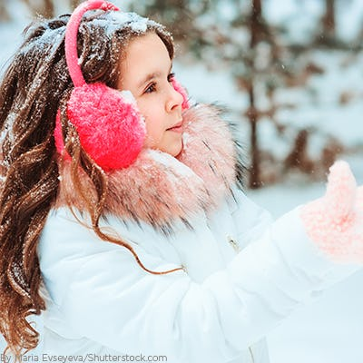Young girl playing in the snow wearing trendy accessories like a pink headband with pom poms to cover her ears and matching glvoes