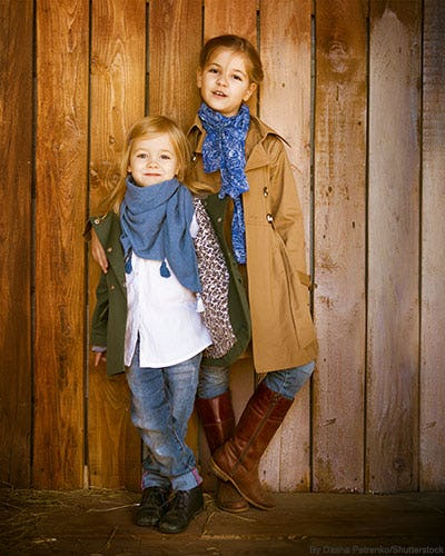 Two fashionable little girls wearing anoraks and scarves.