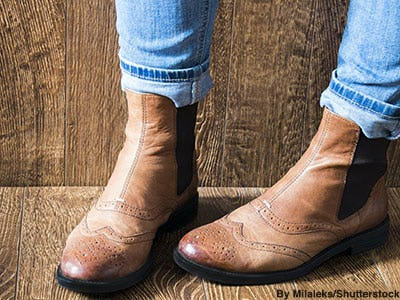 Women's brown leather wing tip Chelsea boots.