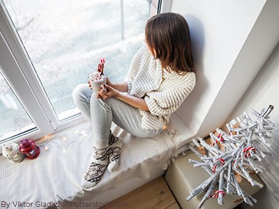 Woman sitting on the window seal in cozy pajamas and socks with hot chocolate and christmas decorations