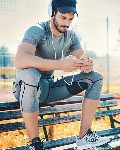 Man wearing work out clothes with running shoes, fitness tracker, and blue tooth headphones