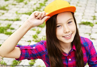 Girl wearing a red and blue plaid shirt and an orange suede baseball hat.