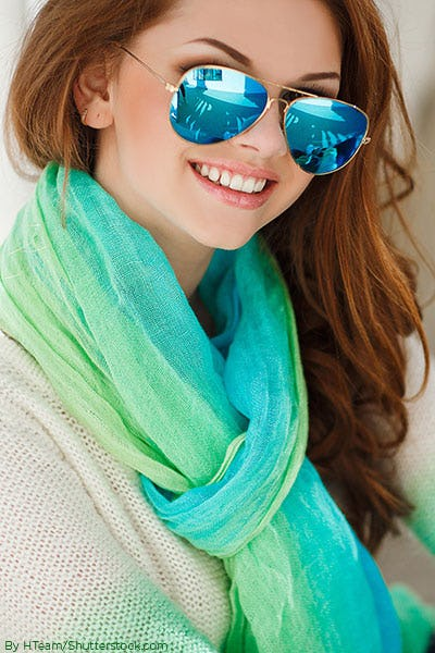 Red headed woman sitting wearing green tinted sunglasses and a green-blue scarf