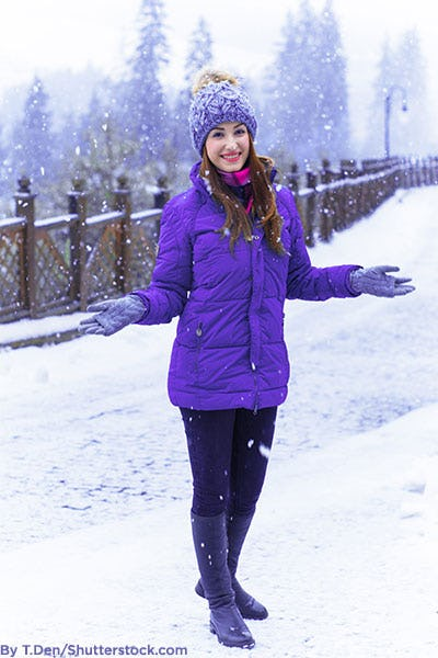 Woman wearing purple winter outfit in the snow.