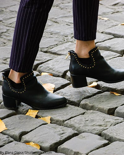 A pair of black ankle booties with gold studs around the ankle