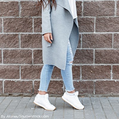 Woman wearing white dad sneakers paired with light denim jeans and long grey sweater.