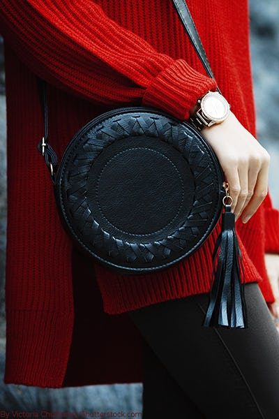 Woman wearing a long chunky red sweater with black leggings and a circle black bag