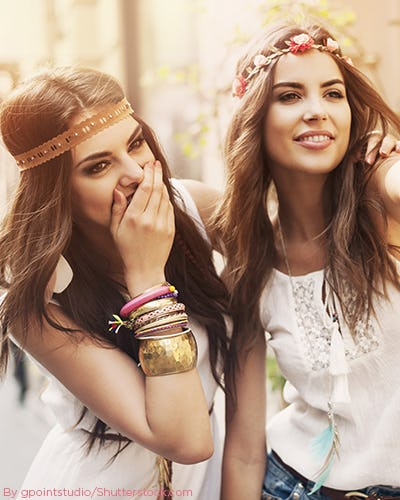 Two woman in boho chic style with flower headbands and arm full of bangles.