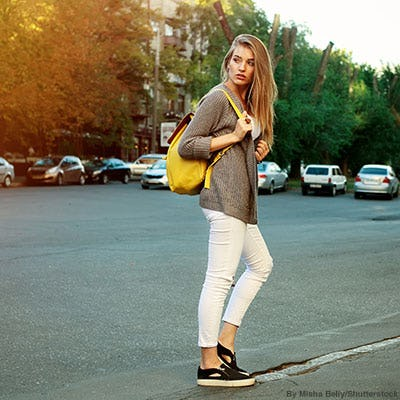 Stylish teen girl wearing taupe sweater, cropped white denim, and a yellow backpack.