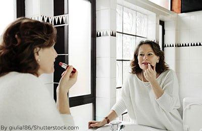 Woman putting on lipstick in her bathroom mirror.