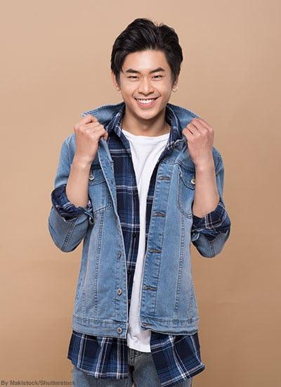 Teen boy wearing a denim jacket, flannel shirt, and white t-shirt.