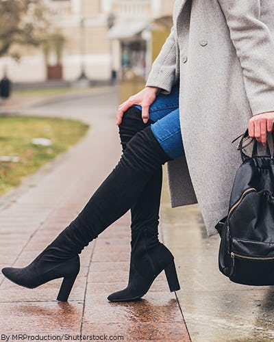 Woman wearing blue jeans with thigh high suede black boots