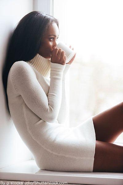 Woman wearing winter white sweater dress.