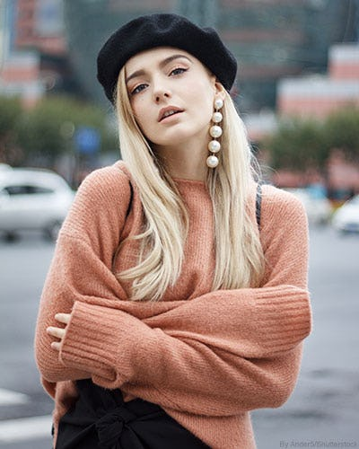 Woman wearing a black beret hat, statement pearl bauble earrings, and a pastel peach sweater.