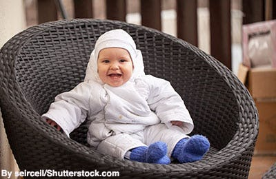 Baby boy in white snowsuit and blue knit booties.