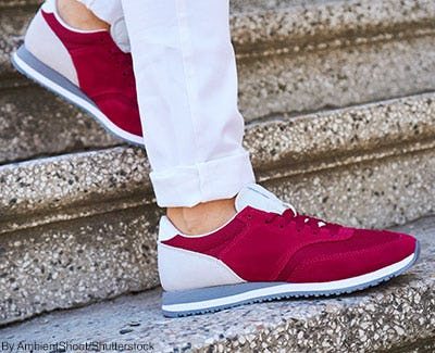 Cuffed white jeans with magenta and cream athletic sneakers.
