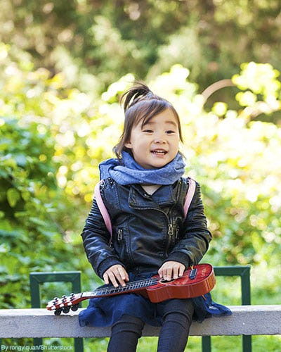 Little girl in black leather jacket and scarf carrying ukulele.