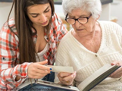 Grandma and granddaughter sitting on a couch looking through a photobook