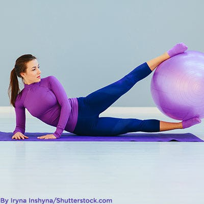 Woman wearing purple activewear while exercising.