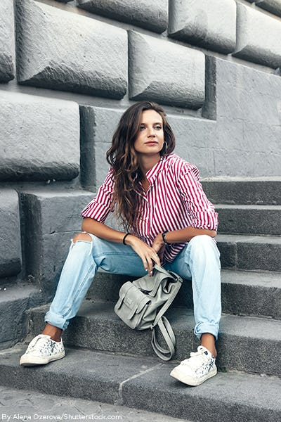 Young brunette girl sitting on stairs wearing blue jeans and a red striped blouse.
