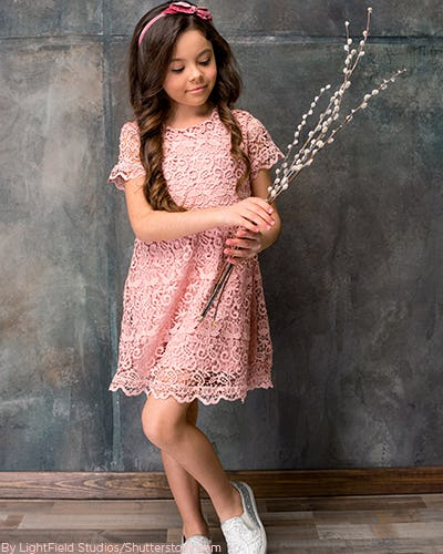 Young girl wearing a light oink lace dress with tennis shoes