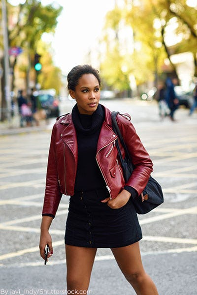 Woman wearing black sweater dress with burgundy leather jacket.