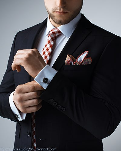 Young man wearing a suit with a check tie and pocket square