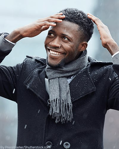 Young man in the snow wearing layers under his black wool coat and a thick knit scarf
