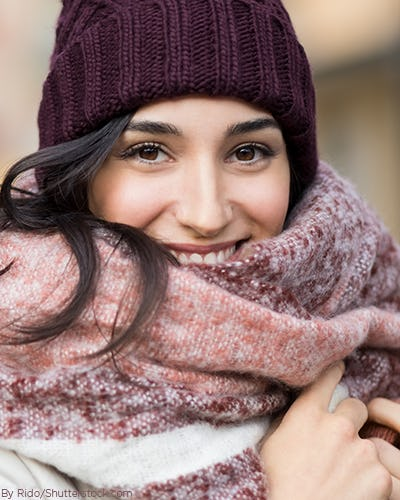 Young woman wearing a maroon beanie and maroon and white blanket scarf wrapped around her neck