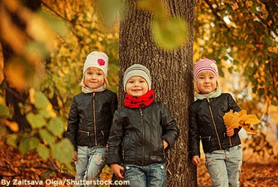Two little girls and a little boy wearing black leather jackets and knit hats in fall.