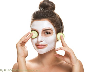 Woman getting a spa treatment facial with cucumbers on her eyes