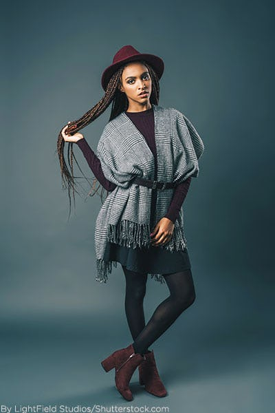 Woman wearing blanket scarf belted over a sweater dress.