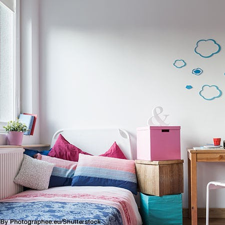 Decorated pink and blue college dorm room with wall decals, plants, storage cubes, and colorful bedding.