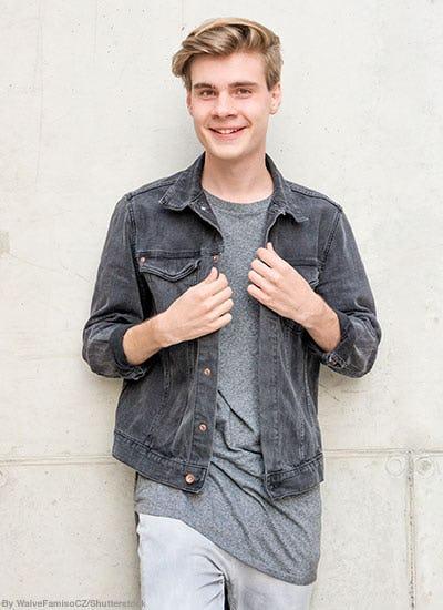Stylish teen boy wearing light gray denim, gray t-shirt, and a dark gray denim jacket.