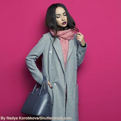 Woman wearing grey chesterfield coat and pink scarf carrying a navy leather handbag.